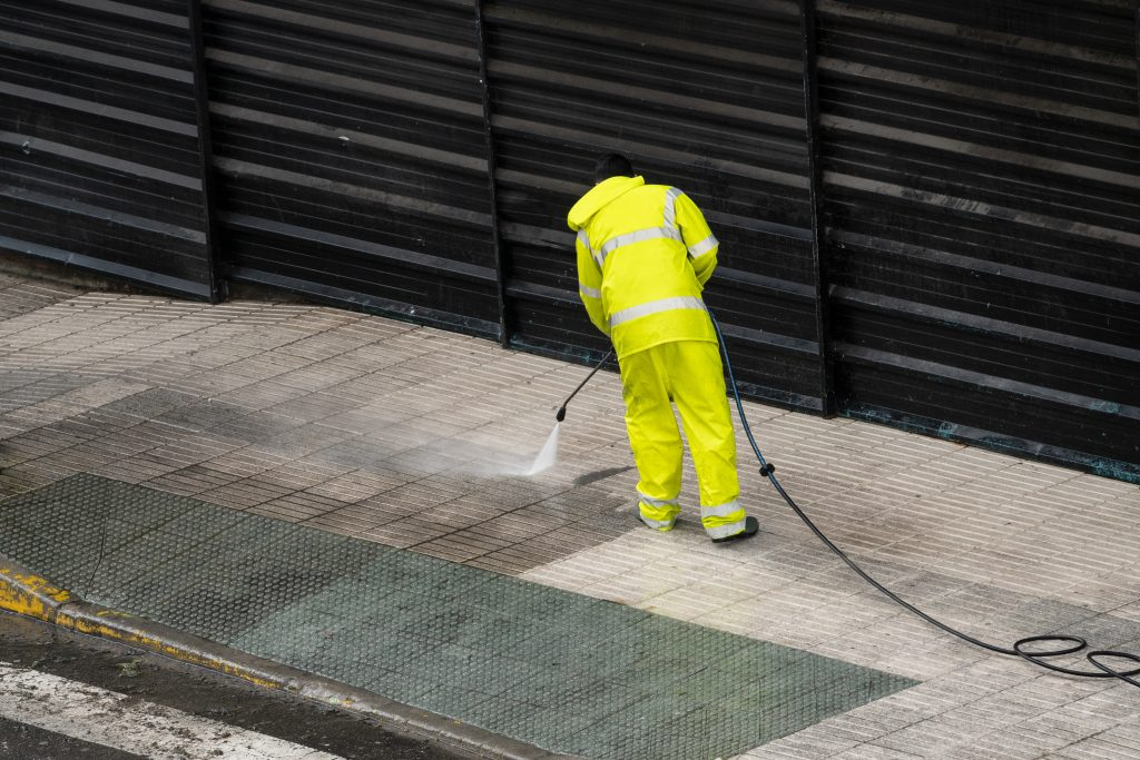 A water blaster being used on a commercial footpath